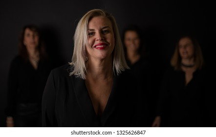 Close-up of woman 50 and dressed in black with friends behind and out of focus