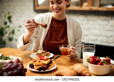 Close-up of woman adding honey on waffles while eating breakfast at home.