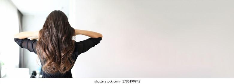 Nahaufnahme einer Frau nach dem Besuch des Frisors. Lange Fluchen der brunette weibliche Person. Hairdo für den Urlaub oder den Alltag. Schönheitssalon und Friseur-Konzept