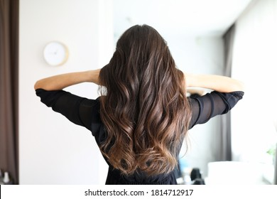 Close-up of woman after visiting hairdresser. Long curls of brunette female person. Hairdo for holiday or for everyday. Beauty salon and hairstyle concept