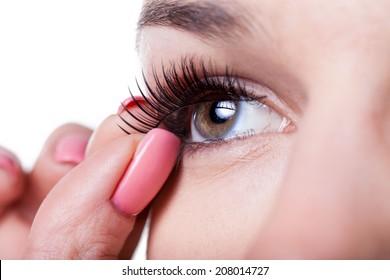 Close-up of a woman applying false eyelashes