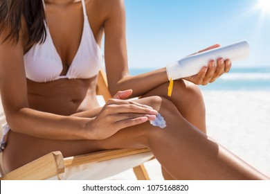 Closeup of woman applying suntan lotion on leg. Closeup of woman hand applying sunscreen cream while sitting on deckchair. Detail of young woman in white bikini applying suntan protection cream.