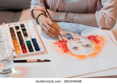 Close-up, woman artist paints picture portrait, orange hair eyes and lips with a butterfly, on the table paints a color palette.