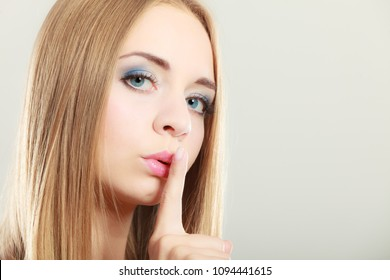 Closeup woman asking for silence or secrecy with finger on lips hush hand gesture, on gray background