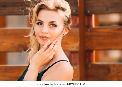 close-up of a woman with a beautiful makeup near a wooden fence