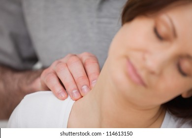 Close-up of a woman being massaged by a physiotherapist in a room