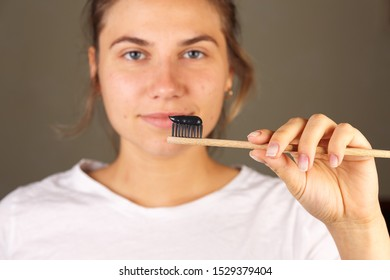 Close-up, a woman black toothpaste, whitening toothpaste, wooden toothbrush with black bristles.