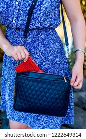 Closeup of a woman in a blue dress holding a leather bag and giving a red purse. The modern concept of fashion and life style.