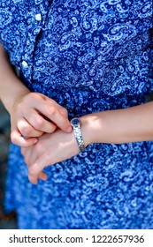 Closeup woman in blue dress looks at the wrist watch. The modern concept of business, fashion and life style.