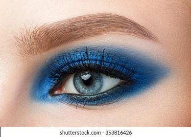 Close-up of woman blue eye with beautiful blue smokey eyes makeup. Modern fashion make-up.