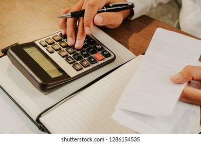 Closeup of woman calculating bills on calculator. Notebook and calculator lying on desk. Accountancy concept. Cropped view.