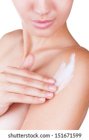 Close-up of a woman cares about her shoulder applying cosmetic cream. Isolated on white background