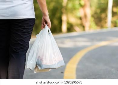 Femme en gros plan portant les sacs en plastique de l'épicerie en marchant dans la rue, concept environnement