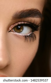 close-up of woman cat eye with golden shadow isolated on black, fashion evening elagance on model eyes