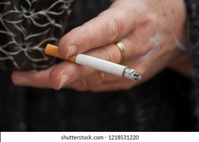 closeup of woman with cigarette in hand in outdoor