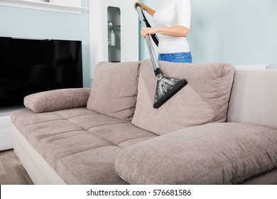 Closeup Of Woman Cleaning Sofa With Vacuum Cleaner At Home
