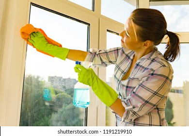 Close-up of woman cleaning windows, hands in rubber protective gloves, rag and sprayer detergent.