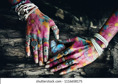 closeup of woman colorful hands with lot of rings on tree surface in heart shape  with butterfly in the middle composite photo