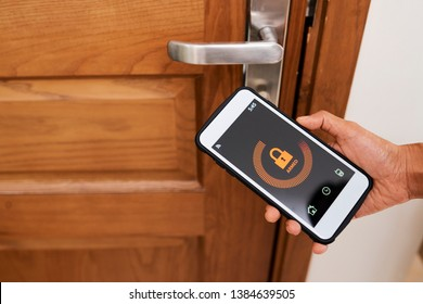 Close-up of woman controlling the security of her house with mobile app on smartphone, she locking the door online