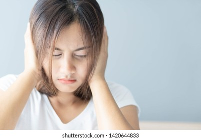 Closeup woman covering ears with her hand, noise problem, selective focus