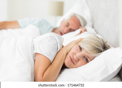 Close-up of a woman covering ears while man snoring in bed at home