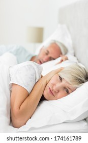 Closeup of a woman covering ears while man snoring in bed at home