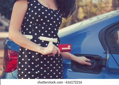Closeup of a woman with credit card opening fuel tank of her new car