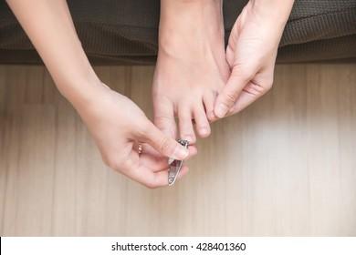 closeup of a woman cutting nails