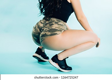 Closeup of woman dancing twerk booty on blue background. Young girl wearing camouflage shorts, black top and running shoes. movement, healthy lifestyle, hobby concepts