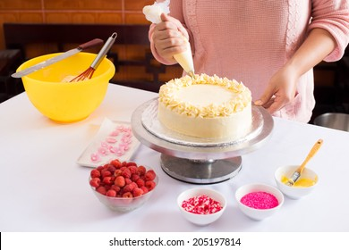 Close-up of woman decorating cake