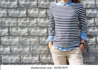Close-up of a woman in a denim shirt, striped t-shirt and beige pants with a fitness tracker at hand on a background of a brick wall outdoors, copy space