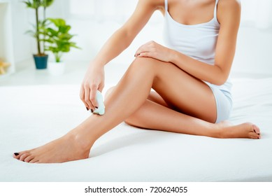 Close-up of a woman depilation her leg with Electric Razor.
