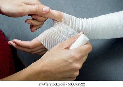 Close-up of woman doctor bandaging a hand.