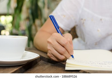 Close-up of a woman drawing into her diary, in the park