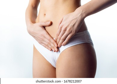 Close-up of woman dressed in underwear suffering from menstrual pain. Isolated on white background.