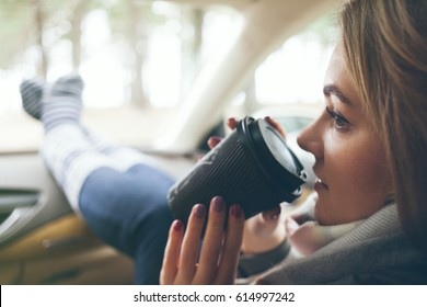 Close-up of a woman drinking take away cup coffee during the road trip in a car. Selective focus, film effect.    Woman feet in warm socks on car dashboard. Drinking take away coffee on road.