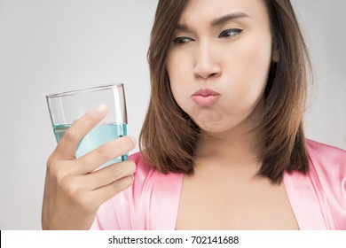 Close-Up Of Woman Drinking Water While Standing Against Wal, People Rinsing And Gargling While Using Mouthwash From A Glass - Dental Healthcare Concepts