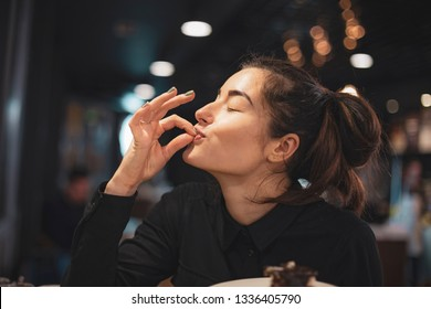 Closeup of woman eating chocolate cake in a cafe. selective focus, noise effect