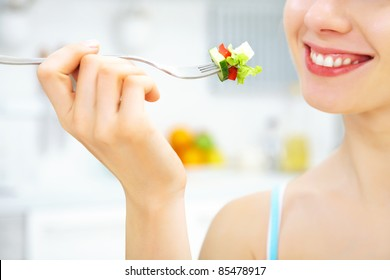 close-up of woman eating fresh salad