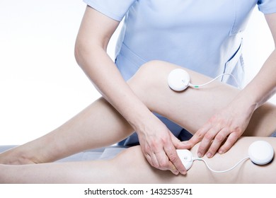 Close-up of woman with electrostimulator electrodes on her legs
