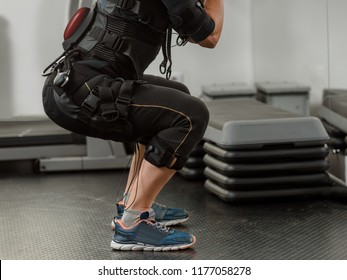 Closeup of woman in EMS suit doing squat exercise
