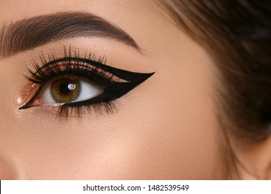 close-up of woman eye with sexy eyeliner and golden shadow, girl's opened eyes with glamorous evening make-up