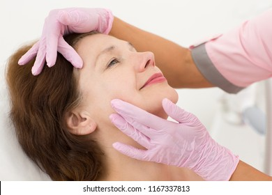 Closeup of woman face during anti aging massage in cosmetology office. Hands in gloves of female doctor cosmetologist touching skin and smoothing wrinkles. Smiling female client enjoying process.