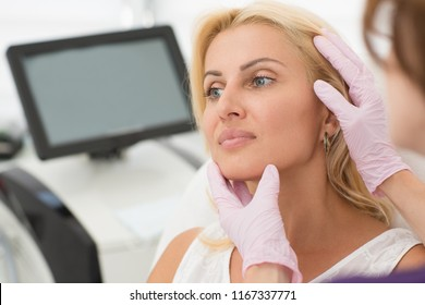 Closeup of woman face during procedure at cosmetology office. Beautiful female client looking away while doctor in gloves examining carefully skin after therapy. Concept of beauty and skin care.