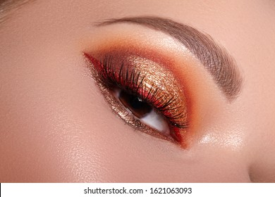 Closeup of Woman Face with Eyes Make-up. Fashion Celebrate Makeup with Red Liner, Gold Shadows, Glowy Clean Skin, perfect Shapes of Brows. Macro of Female Eye. Halloween Style