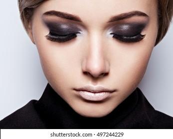 Closeup woman  face with long black lashes. fashion makeup. Beautiful woman face with  black mascara.