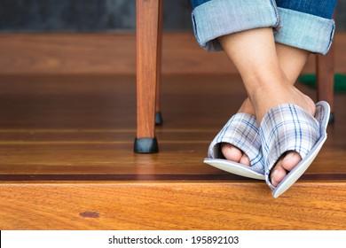 Closeup woman feet in cloth slippers on clean wood floor