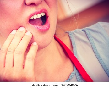 Closeup of woman female suffering from toothache tooth pain.