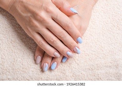 Close-Up Of Woman Fingers With Nail Art. Woman Hand With Beige and Blue Nail Polish. Selective focus