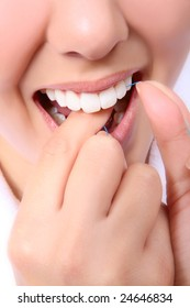 A close-up of a woman flossing her teeth